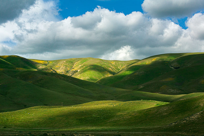 puffy clouds over rolling green hills