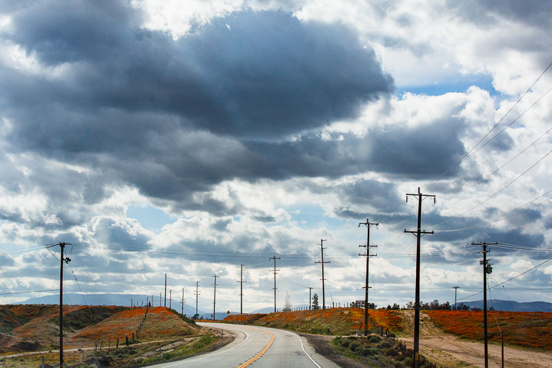 big clouds over telephone poles road