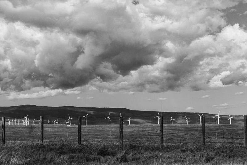 black and white big clouds over windmills
